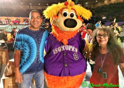 people posing with Isotopes mascot