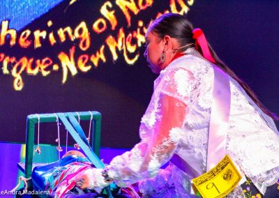 Miss Indian World contestant swaddling a baby