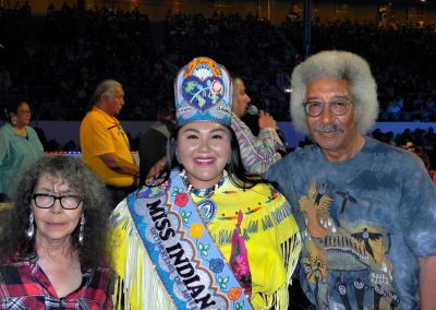 Miss Indian World smiling with two people